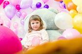 Симпатичная девушка позирует в игровой комнате на фоне воздушных шаров — Стоковое фото