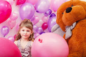Beautiful curly girl posing among pink balloons — Foto Stock