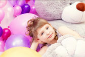 Shot of gray-eyed little girl lying on teddy bear — ストック写真