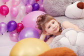 Funny little girl posing lying on big plush bear — Stock Photo