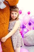 Happy little girl posing hugging big teddy bear — Stockfoto