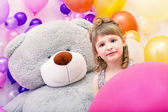 Portrait of blue-eyed girl with big teddy bear — Stock Photo