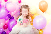 Adorable curly girl posing on balloons backdrop — Stock Photo