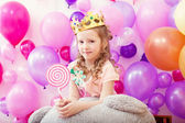 Lovely curly girl posing in crown with lollipop — Stock Photo
