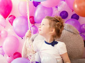 Sympathetic little girl holding bunch of balloons — Foto Stock