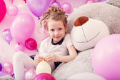Smiling girl sits leaning on big teddy bear — Stock Photo