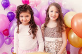 Two merry girlfriends posing on balloons backdrop — Stock fotografie