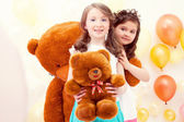 Pretty sisters posing with teddy bears in playroom — Stock Photo