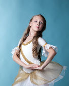 Proud young ballerina posing on blue backdrop — Stock Photo