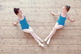 Two little ballerinas posing on wooden floor — Stock Photo