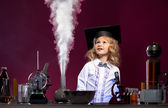 Surprised cute girl looking at evaporation reagent — Stock Photo