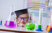 Funny little blonde looks on flasks with reagents — Stock Photo