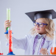Cute little scientist interested looking at flasks — Stock Photo #49889921