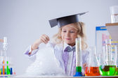 Smiling cute chemist watching chemical reaction — Stock Photo