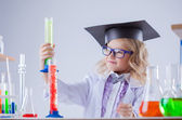 Cute little scientist interested looking at flasks — Stock Photo