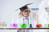 Smiling little chemist puts experiments in lab — Stock Photo