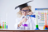 Curious schoolgirl pouring reagent into flask — Stock Photo