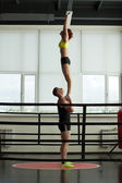 Strong acrobat holding his slender partner in gym — Stock Photo