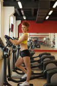 Smiling young runner posing at camera in gym — Stock Photo