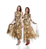 Charming women posing in dresses from same cloth — Stock Photo