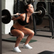 Beautiful girl exercising squatting with barbell — Stock Photo #51193949