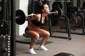 Beautiful girl exercising squatting with barbell — Stock Photo