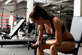 Hot brunette exercising in fitness center — Stock Photo