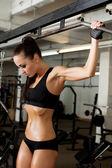 Hot brunette pulls on crossbeam in gym — Foto de Stock