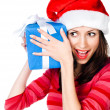 Girl in Santa hat with gifts — Stock Photo