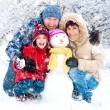 Stock Photo: Happy family with snowman