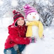 Little girl and snowman — Stock Photo