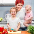 Mother and daughters in the kitchen — Stock Photo