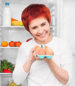 Woman against the refrigerator — Stock Photo