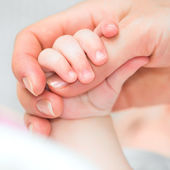 Baby holds mother's finger — Stock Photo