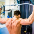 Bodybuilder with simulator — Stock Photo