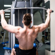 Bodybuilder with simulator — Stock Photo #37787187