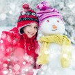 Girl and snowman — Stock Photo