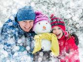 Famiglia con un pupazzo di neve — Foto Stock