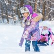 Two cute girls sledding — Stock Photo