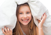 Směje se holčička pod přikrývkou — Stock fotografie