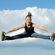 Beautiful girl in gymnastic jump against blue sky — Stock Photo #12613402