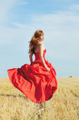 Running bride in red wedding dress in a field — Stock Photo