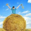 Man on a stack of straw against a field — Stock Photo