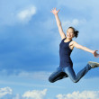 Beautiful girl in gymnastic jump against blue sky — Stock Photo