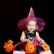 Halloween baby witch with a carved pumpkin — Stock Photo