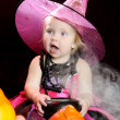 Halloween baby witch with a carved pumpkin over black background — Stock Photo #13511601