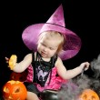 Stock Photo: Halloween baby witch with a carved pumpkin over black background