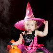 Halloween baby witch with a carved pumpkin over black background — Stock Photo #13512404