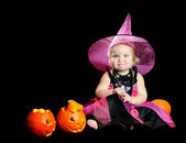 Halloween baby witch with a carved pumpkin over black background — Stock Photo