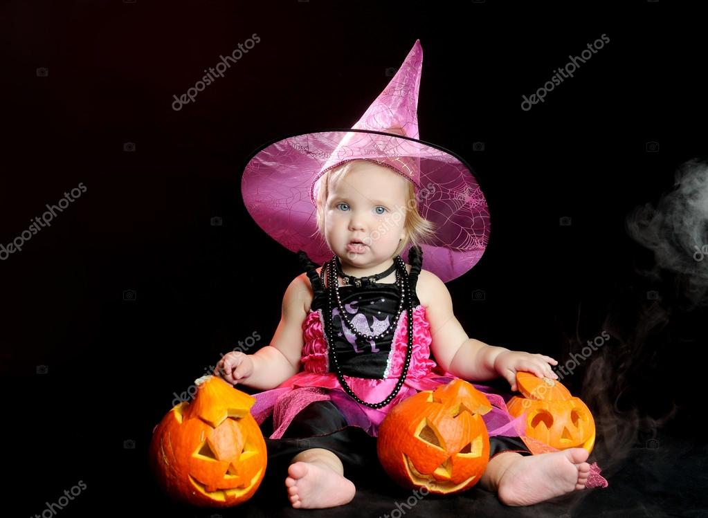 Halloween baby witch with a carved pumpkin over black background — Stock Photo #13511434